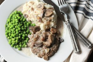 Salsbury Steak with a creamy brown gravy, served with mash potatoes and green peas.