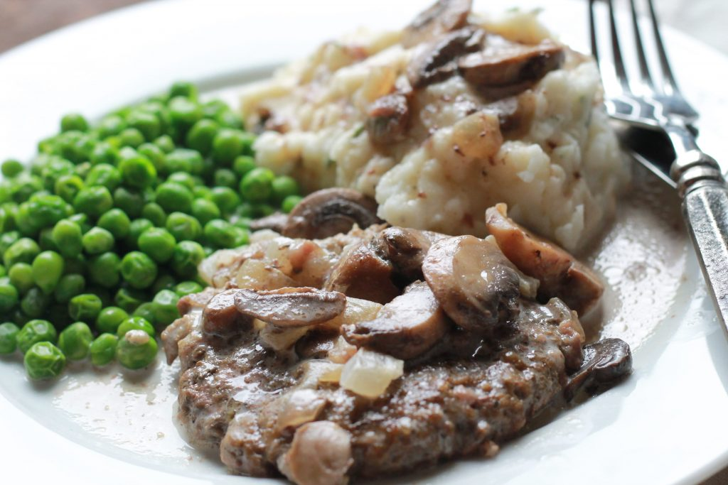Slow Cook Salisbury Steak in Cream Gravy with a side of green peas, and mashed potatoes served on a white plate with a silver fork and knife