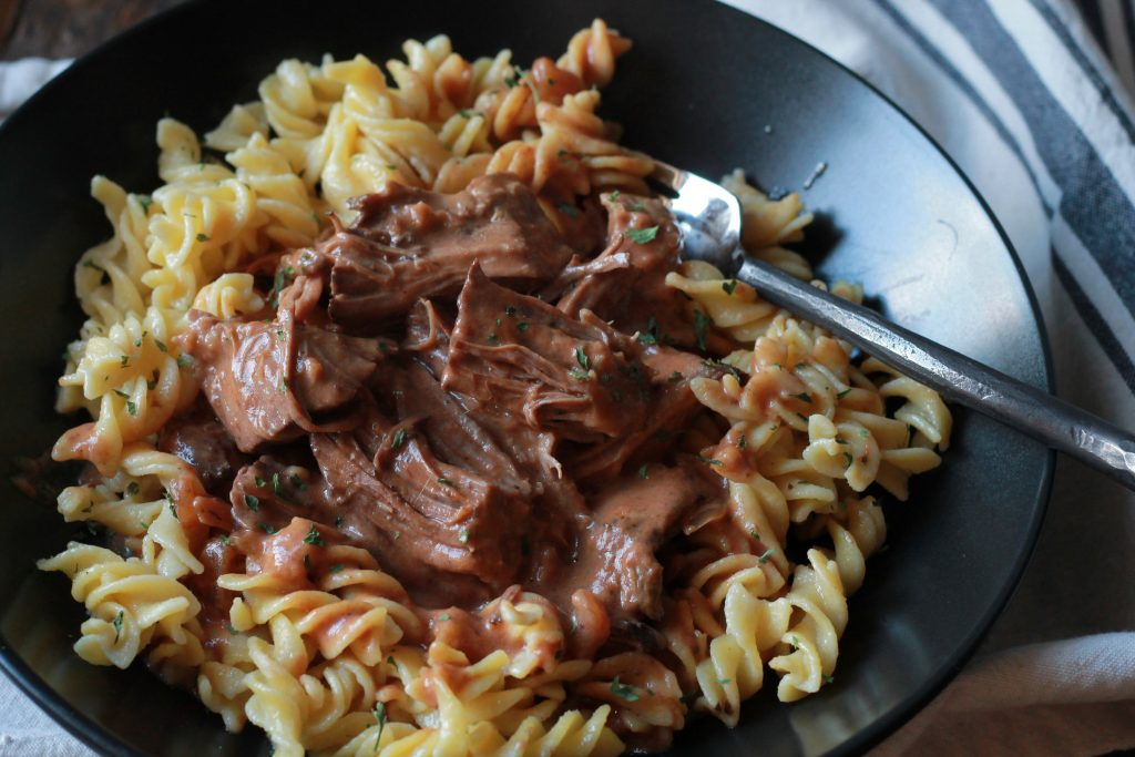 slow cooked beef with creamy seasoned sauce served on top of cooked pasta in a black bowl.