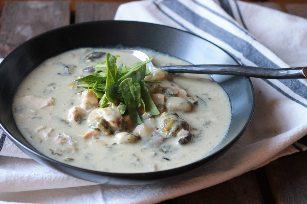 Creamy Chicken Gnocchi Soup served with mushrooms and topped with green spinach leaves in a black bowl served with a spoon