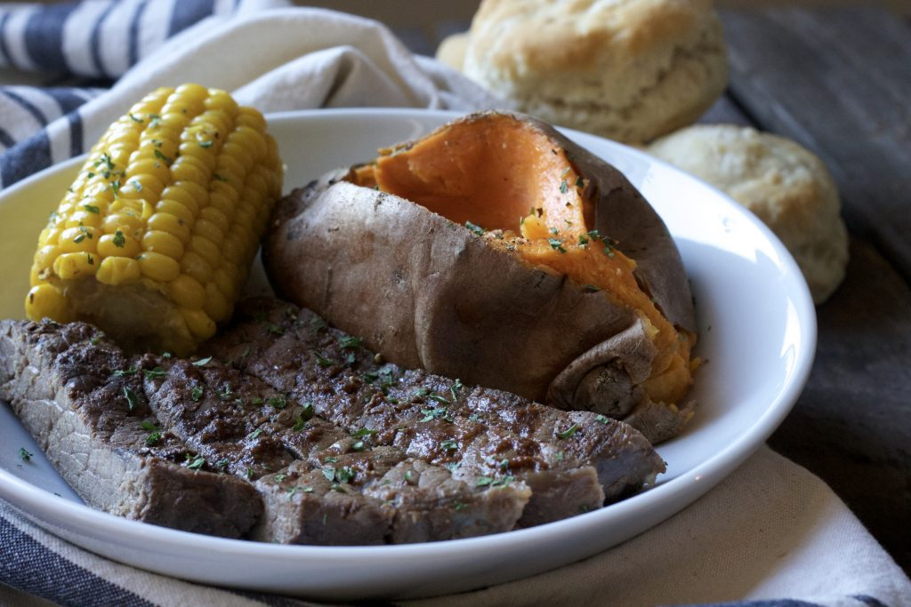 Tender seasoned steak served with a petite ear of corn and one cooked sweet potato on a white plate. With a side of biscuits on a white and blue napkin.