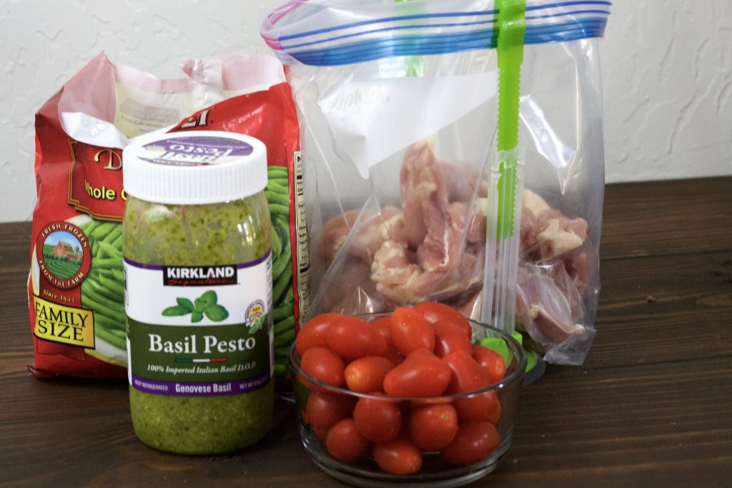 chicken in a clear plastic bag standing up with green tongs stand. paired with a side of red petite tomatoes with a jar of basil pesto with a bag of frozen green beans all on a wooden surface