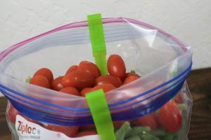 one green Jokari Hands-Free Bag Holder with a clear zip lock bag filled with petit red tomatoes and frozen green beans.