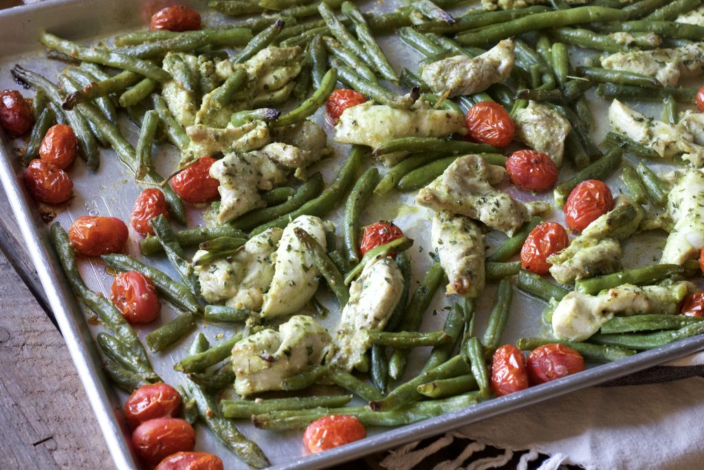 mixed chicken with green beans, petite tomatoes all dressed in basil pesto sauce in one pan ready to be cooked.