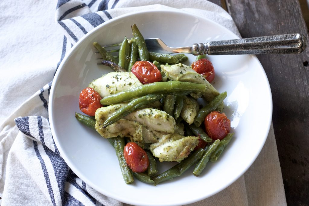 mixed chicken with green beans, petite tomatoes all dressed in basil pesto sauce served in a white bowl with a silver fork