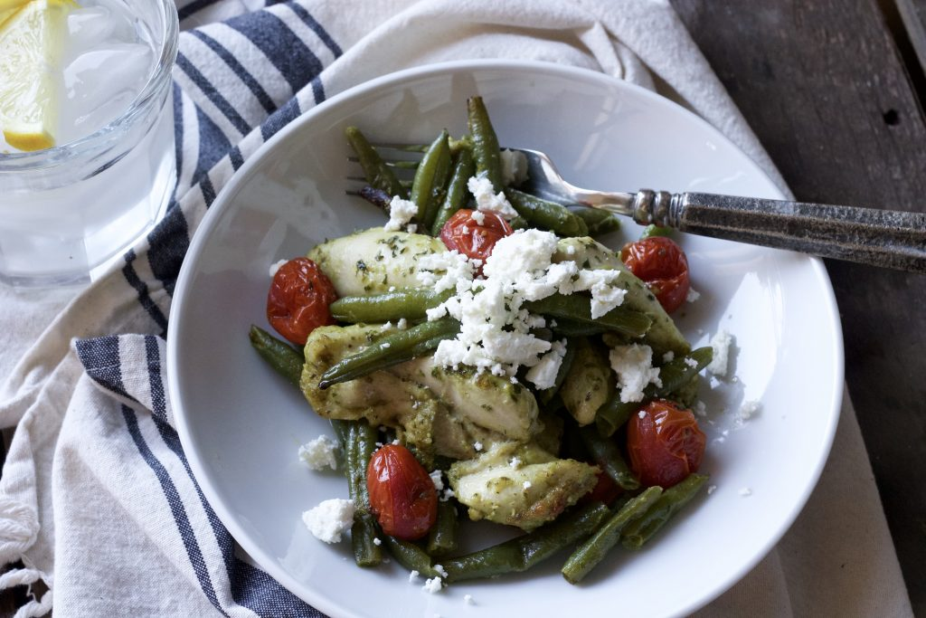 mixed chicken with green beans, petite tomatoes all dressed in basil pesto sauce served in a white bowl with a silver fork topped with parmesan cheese