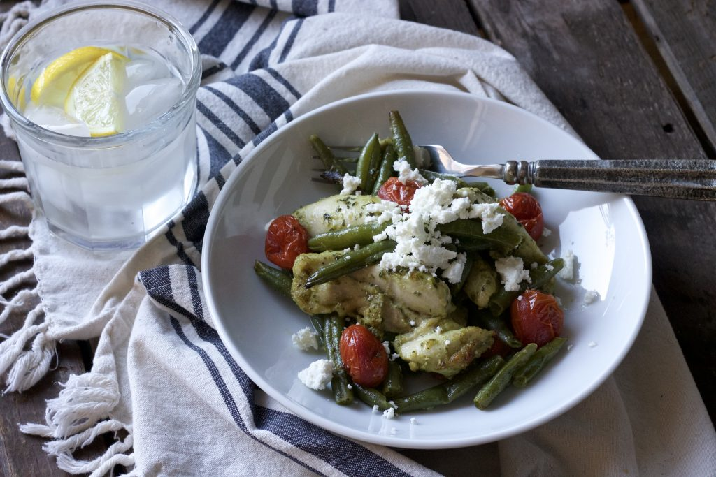 mixed chicken with green beans, petite tomatoes all dressed in basil pesto sauce served in a white bowl with a silver fork topped with parmesan cheese with a glass of lemon water