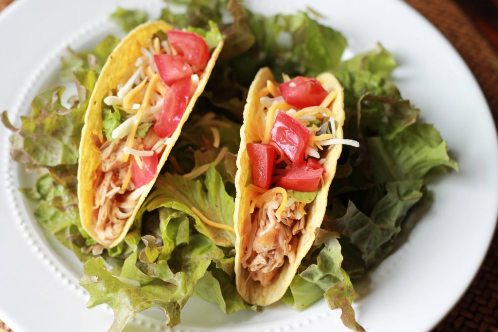 Two chicken tacos, topped with lettuce, diced tomatoes, and shredded cheese, served on a plate filled with lettuce.