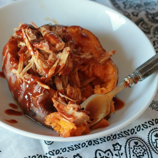 sweet potatoe with shredded chicken and BBQ sauce in a white bowl and silver fork all served on a white bandana