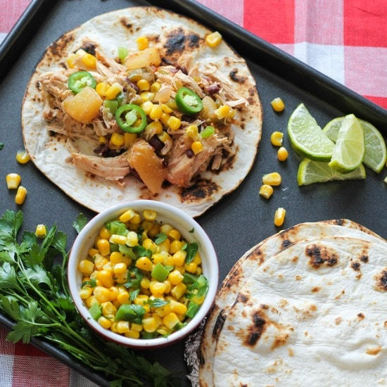 chicken, and diced pineapples, with jelopanos,and corn on a crisp flour tortilla, on a one pan baking sheet with lies and a side of corn and green peppers in a red bowl, with a side of cilantro.