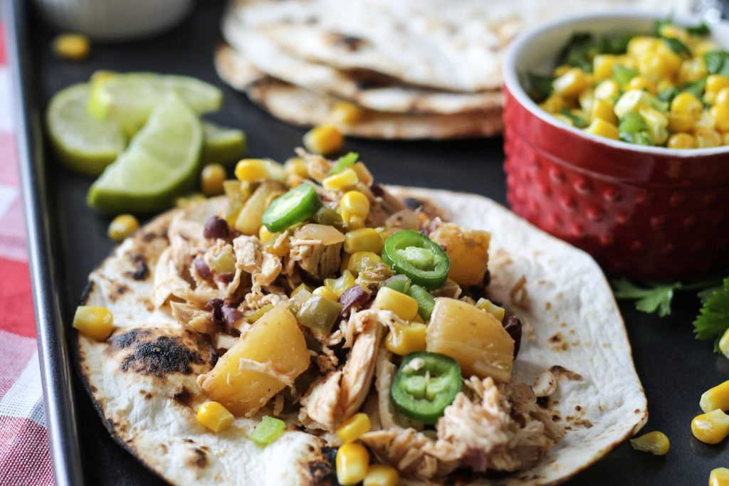 chicken, and diced pineapples, with jelopanos,and corn on a crisp flour tortilla, on a one pan baking sheet with lies and a side of corn and green peppers in a red bowl.