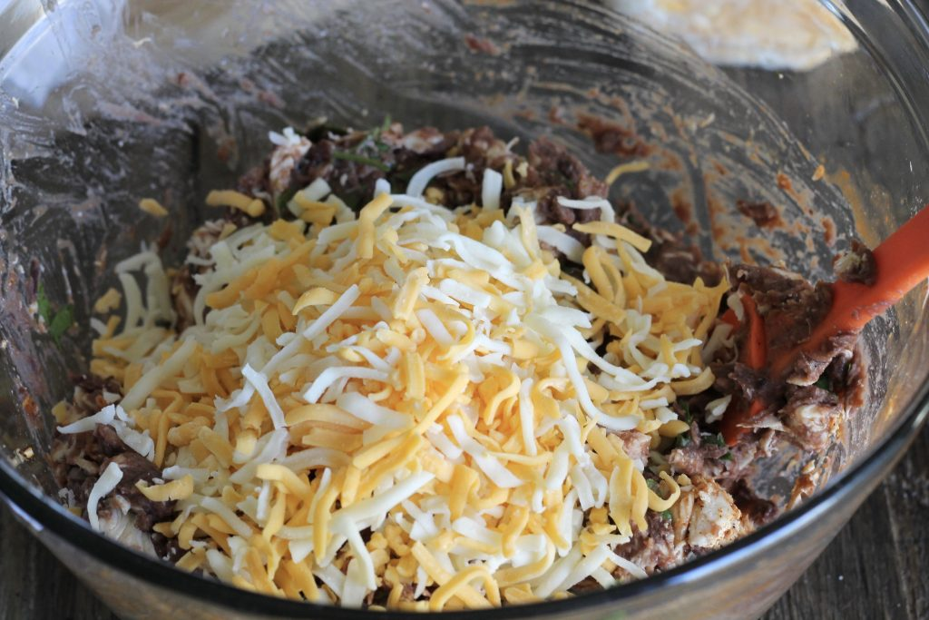 shredded roasted chicken, taco seasoning, too sauce, cilantro, and refried beans all in a clear bowl mixed and topped with shredded Mexican style cheese.