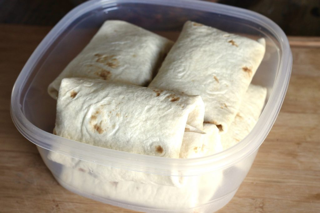 shredded chicken burritos all wrapped up placed in a clear plastic container.