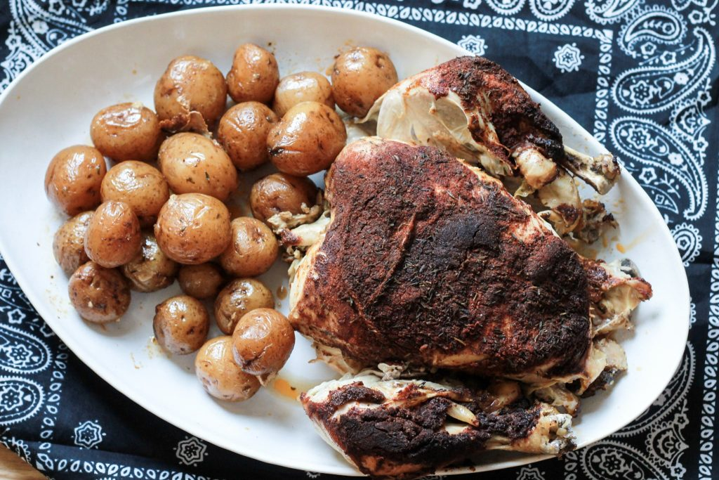 Slow roasted chicken served with petite yellow potatoes on a white plate.