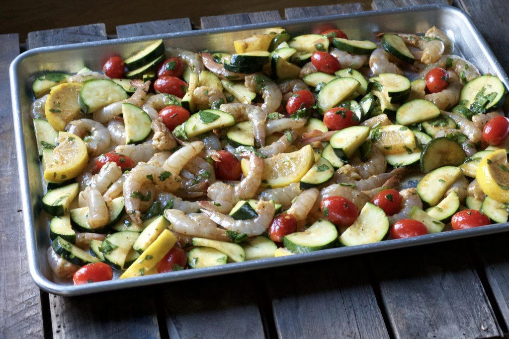 shrimp cooked with lemon slices, petite tomatoes,sliced zucchini, all in one pan on a wooden table.
