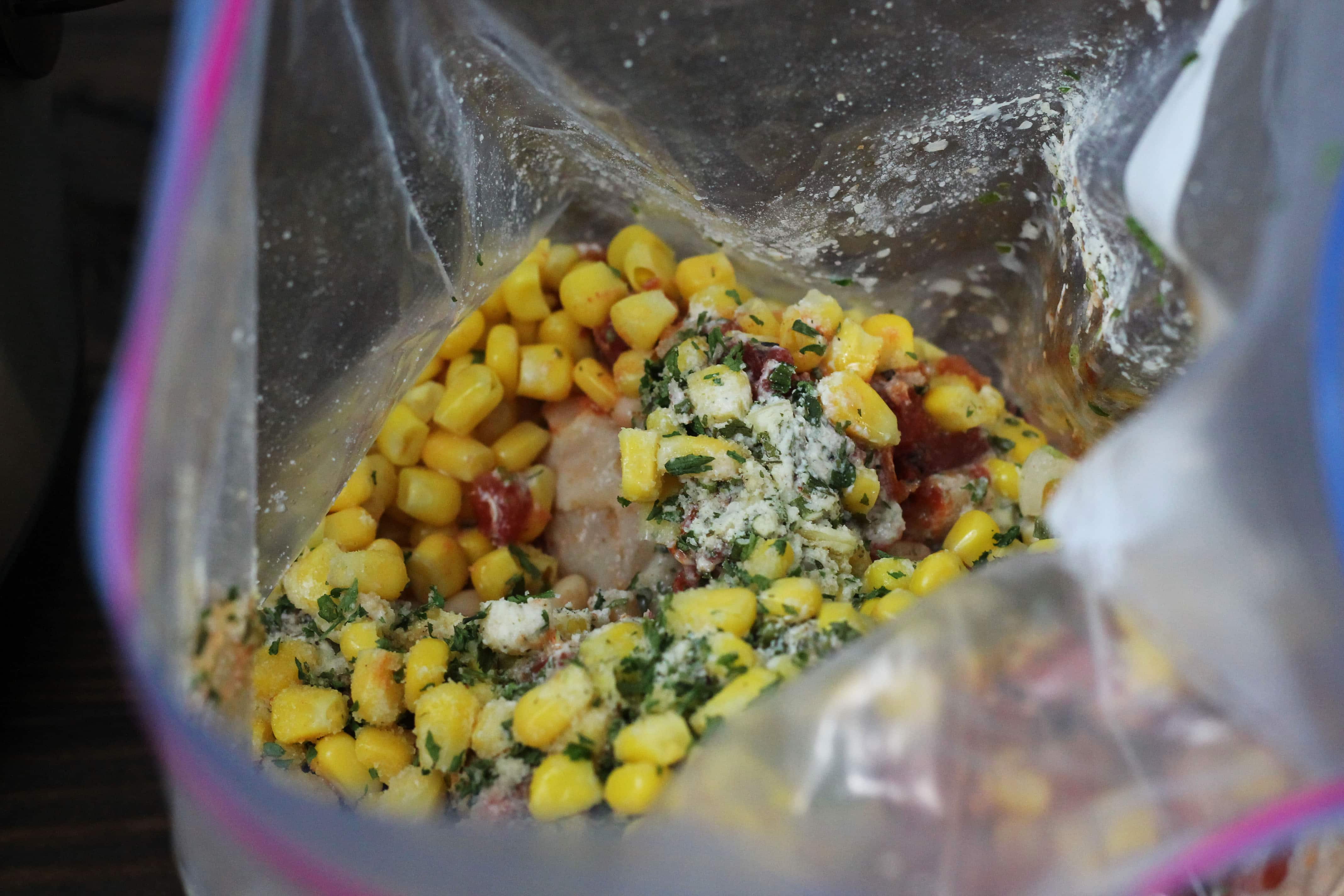 corn with uncooked chicken with feta cheese and cilantro, with red tomatoes, in a clear zip lock baggie.