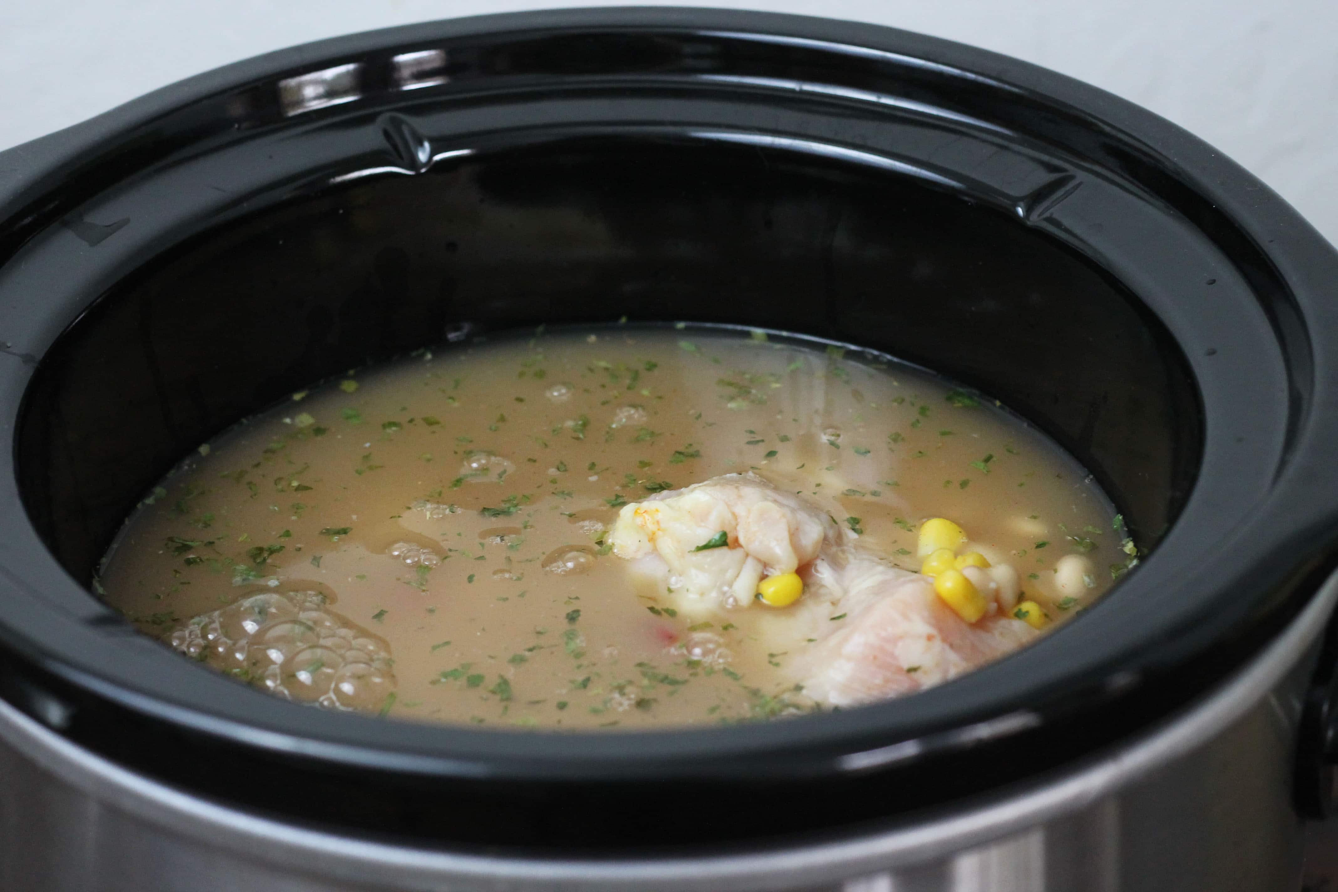 uncooked chicken soaking in chicken broth with corn Diced tomatoes and cilantro in a black crock pot.