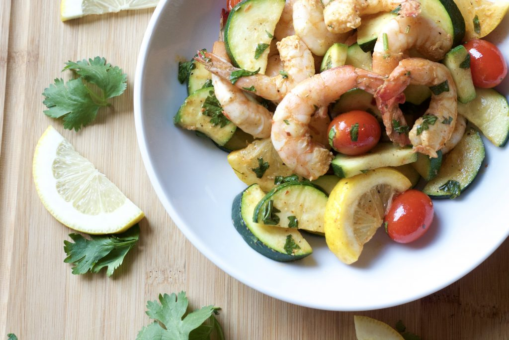 cooked shrimp with lemon slices, petit tomoates, with sliced zucchini topped with cilantro in a  light blue bowl on a wooden table with a slice of lemon and pieces of cilantro on the table.