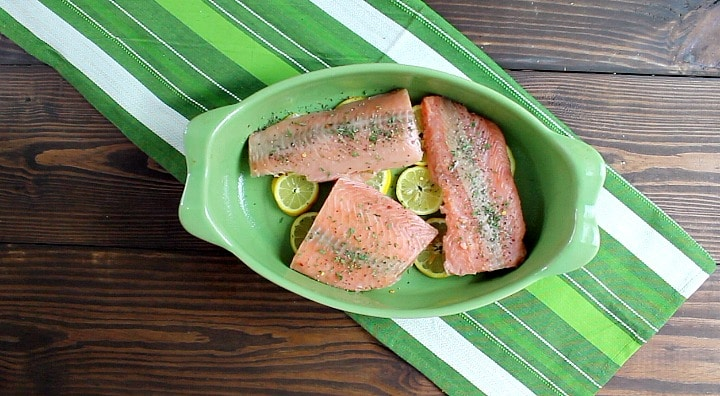 seasoned uncooked salmon in a green dish with lemon slices ready to be cooked in the oven resting on a green place mat.