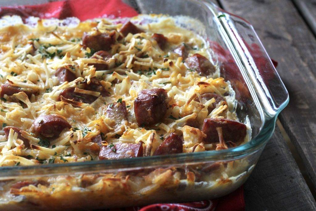 Close up view of a one pan dish with baked cheese, sausage and hashbrown casserole.