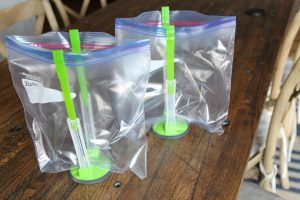 two green Jokari Hands-Free Bag Holders, holding up clear zip lock gallon bags on a wooden table
