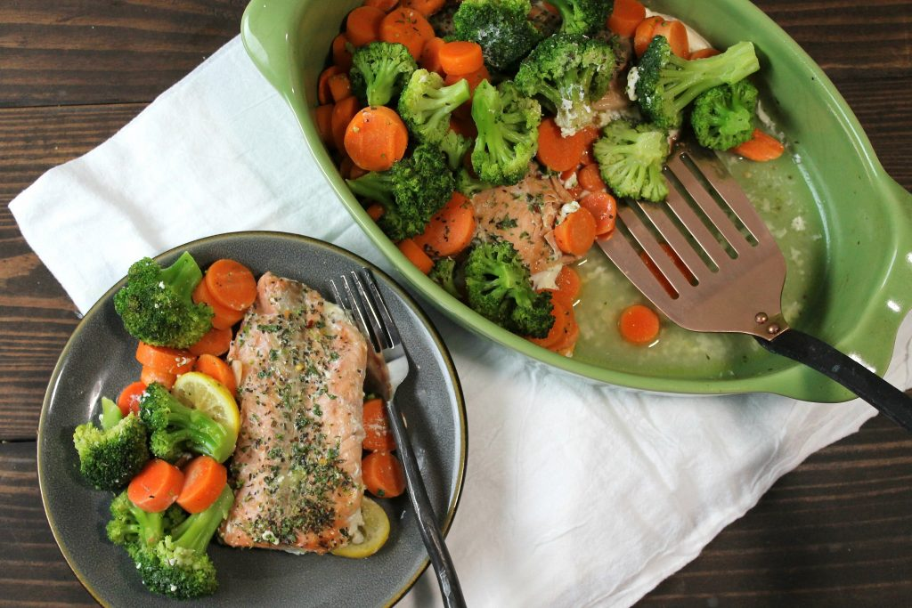 cooked and seasoned salmon with broccoli and sliced carrots served out of a green one dish on to a grey plate.