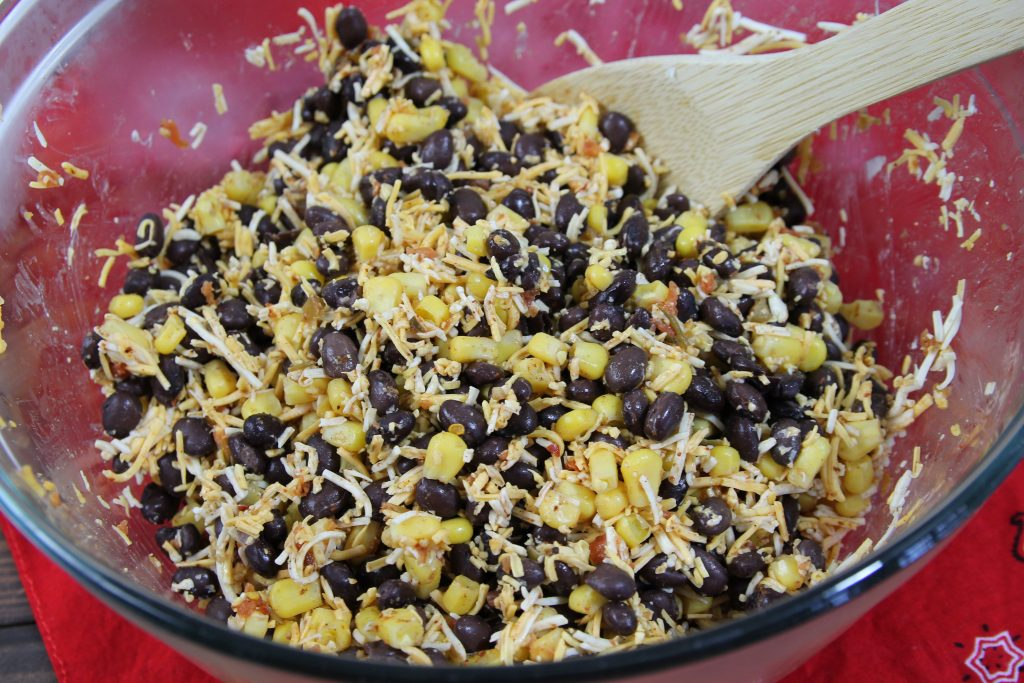 black bean,corn, and shredded cheddar cheese mix, in a glass bowl with a wooden string stick on a red bandana .