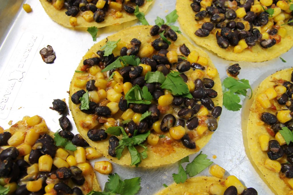 black beans corn and shredded cheese on a crispy tostada topped with green cilantro on a silver baking sheet.