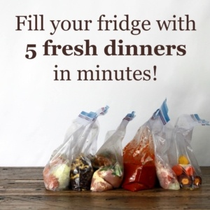 "5 freezer ziplock baggies filled with individual dinners on a wood table. Banner above baggies says ""fill your fridge with 5 fresh dinners in minutes"""
