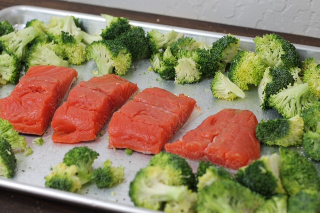 uncooked salmon and raw broccoli on one pan silver baking sheet.