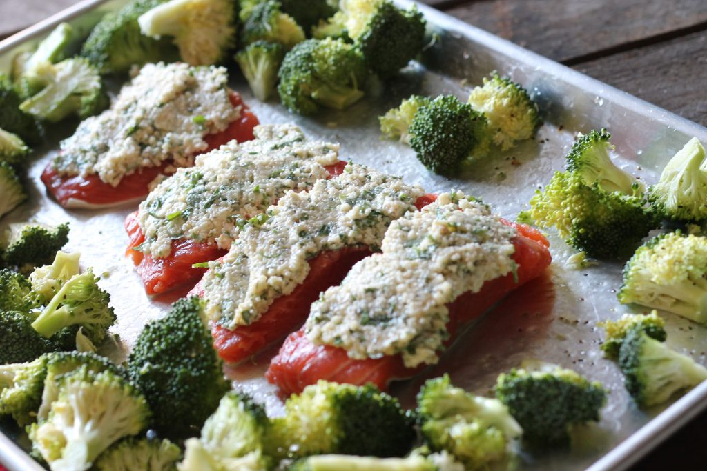 uncooked salmon and raw broccoli topped with mayonnaise, parmesan cheese, almond meal, parsley and lemon all in one pan silver baking sheet.