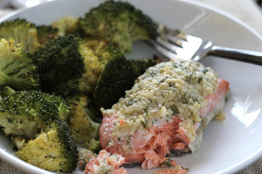 cooked broccoli and salmon topped with mayonnaise, parmesan cheese, almond meal, parsley and lemon, served on a white plate with a silver fork.