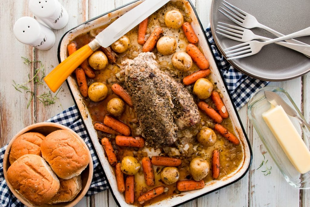 Cooked seasoned pork tenderloin served in a pan with carrots, and sliced potatoes in a baking dish with dinner rolls, forks and plates