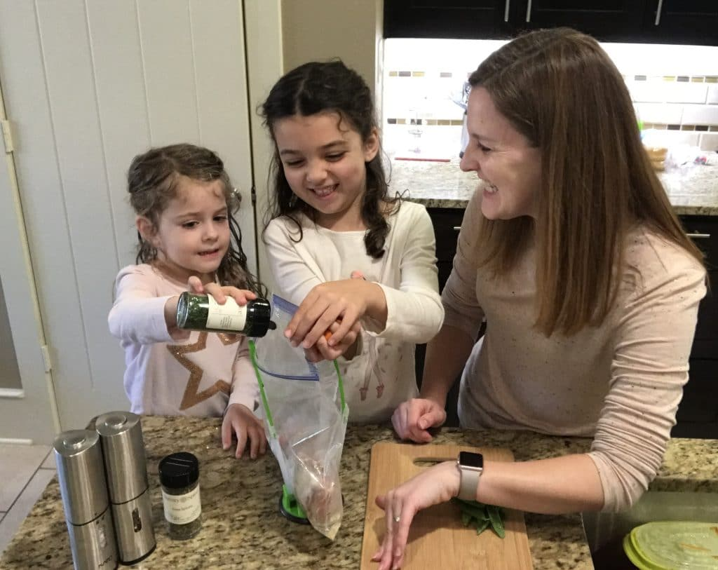 A Mom with her two daughters in the kitchen cooking, and laughing while preparing dinner .