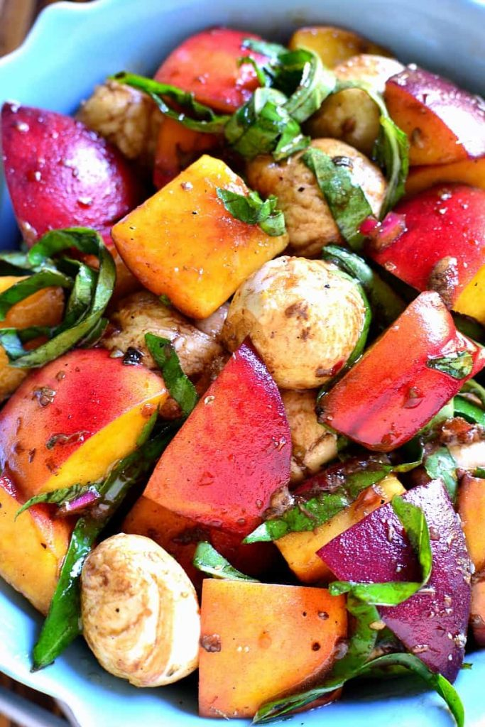 Sliced peaches, lettuce, and petite potatoes together and served on a plate.