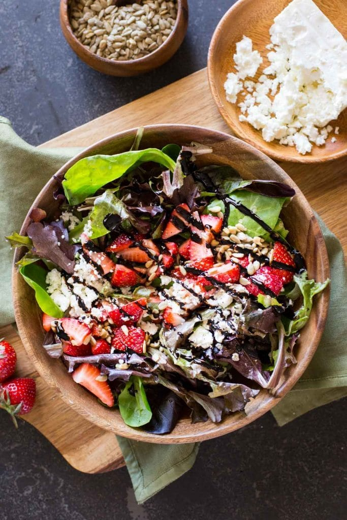 Spinach and greens salad topped with chopped strawberries,nuts and feta cheese with balsamic vinegar in a bowl.