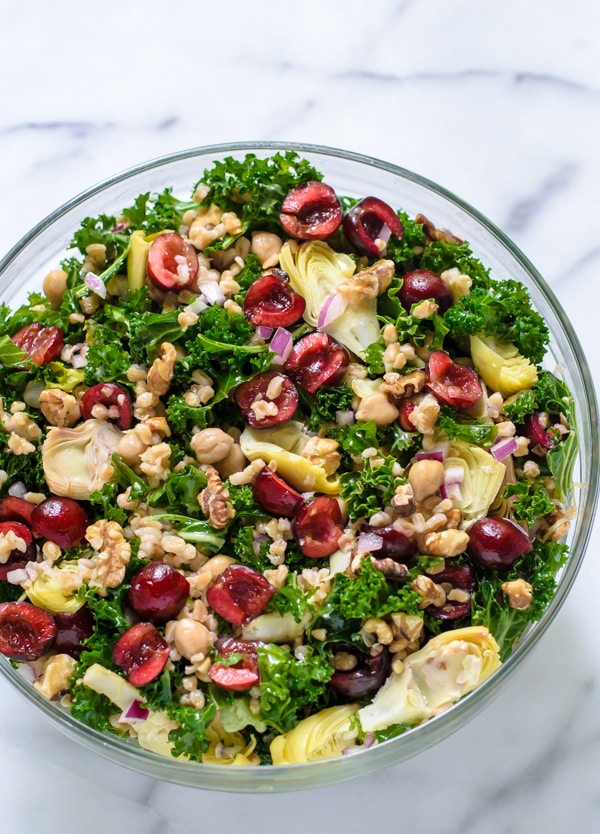 A kale salad in a clear bowl served with chicken, kale, walnuts, cherries, and quinoa.