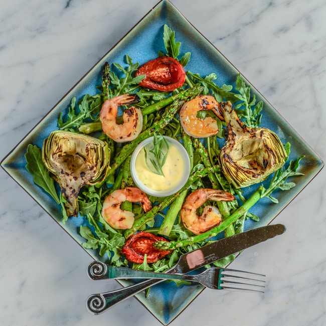 Grilled shrimp, artichokes, asparagus, and mixes it into an arugula salad with a homemade aioli served on a plate.