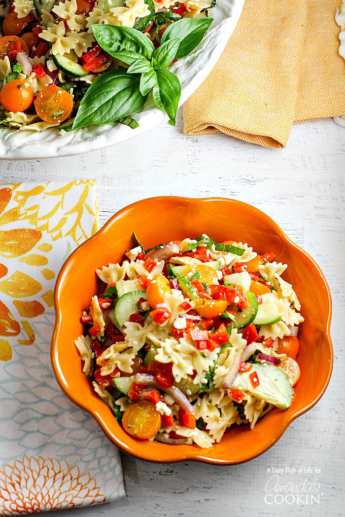 Pasta salad served in a bowl with tomatoes, and cucumbers.