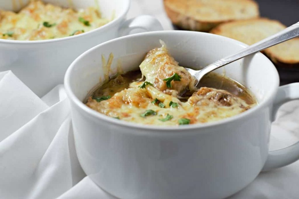 cheesy french onion soup in a white mug with green onion and melty cheese