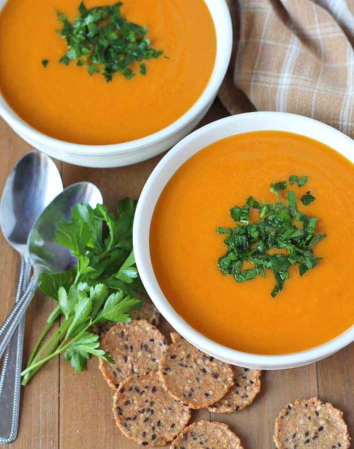 Butternut Squash Sweet Potato and Carrot Slow Cooker Soup in white bowls with parsley sprinkle spoons and crackers