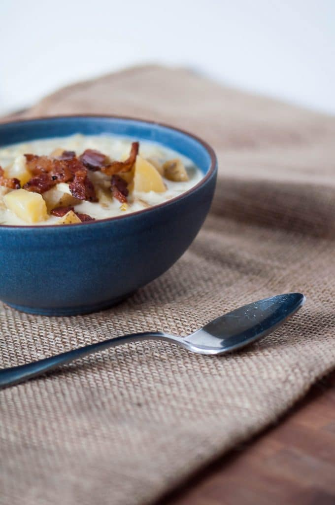 Slow cooker potato corn chowder soup in a blue bowl with bacon and a spoon