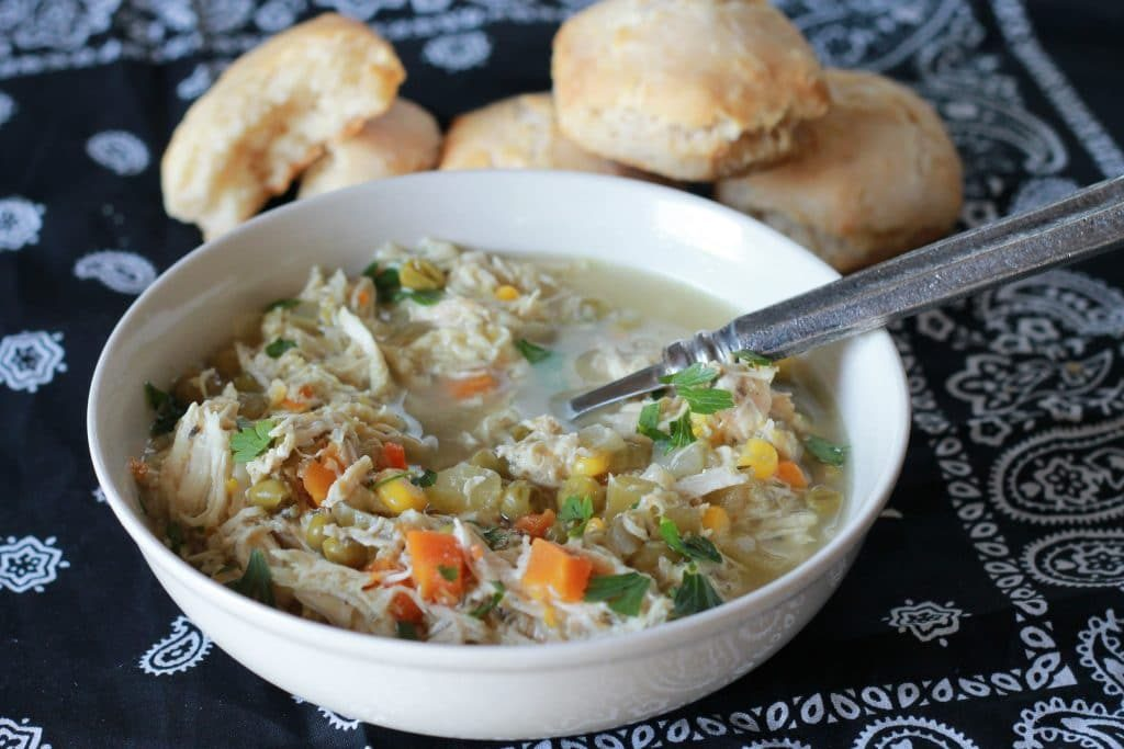 Slow cooker chicken pot pie soup with veggies and biscuits in a white bowl
