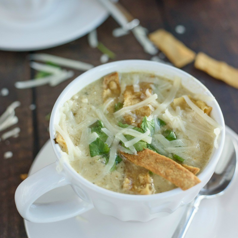 Slow cooker chicken enchilada soup in a mug with melted cheese and crunchy tortilla strips