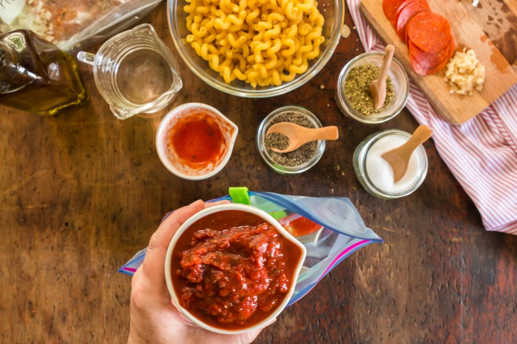 hand holding small white measuring cup with pizza sauce pasta and seasonings