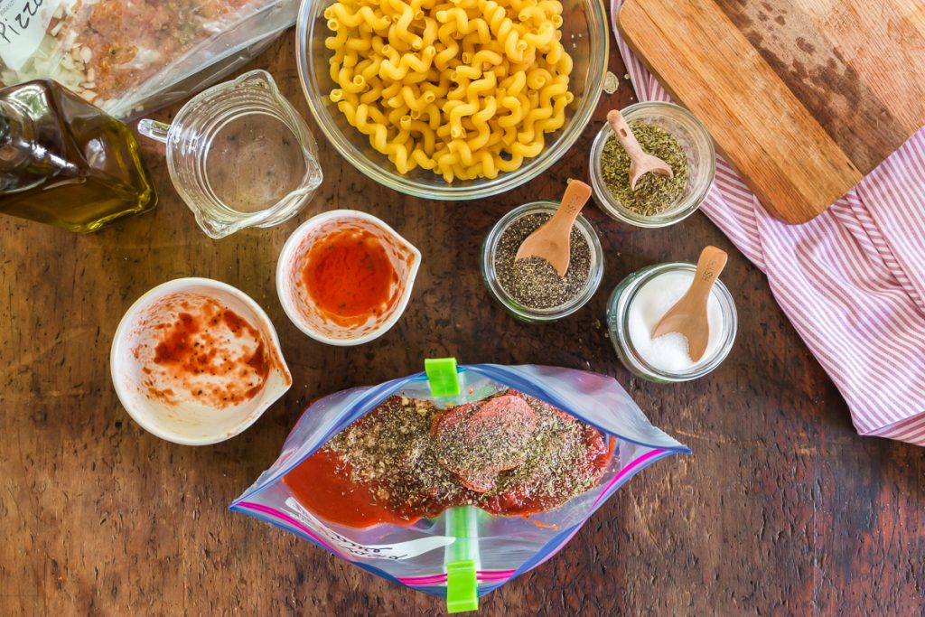 pasta, seasonings, baggie with food and wood cutting board