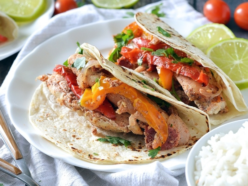 slow cooker chicken fajitas with yellow and red bell peppers in flour tortillas on a white plate