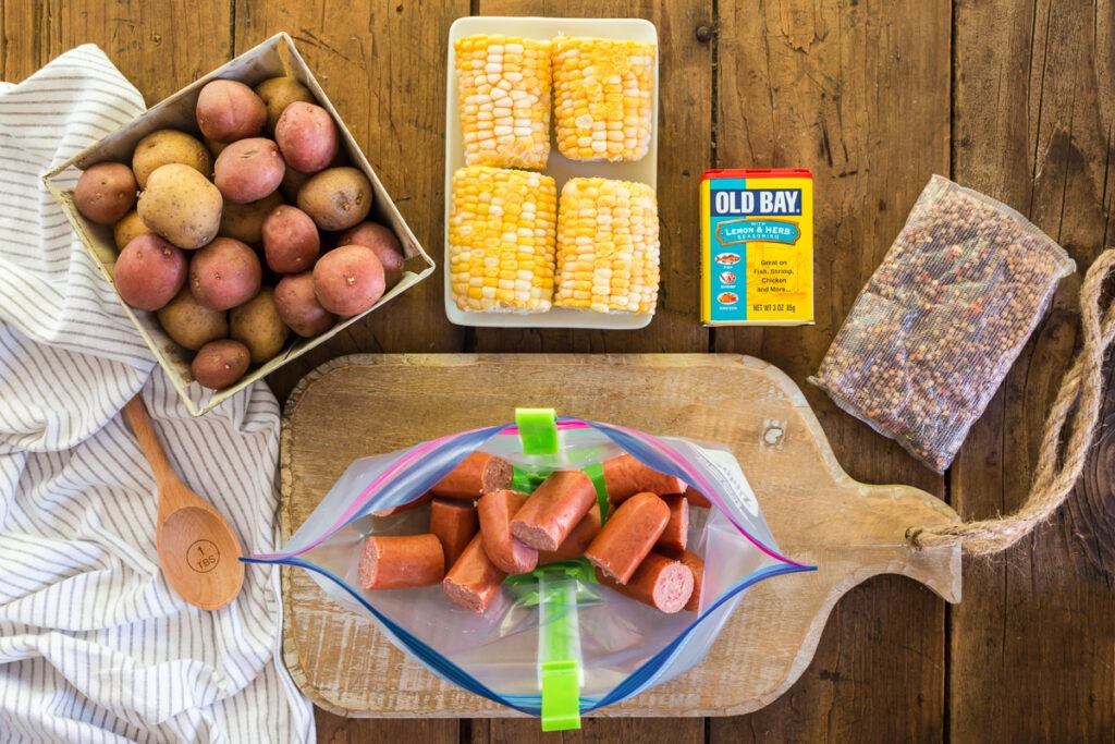ingredients for slow cooker shrimp boil: potatoes, corn on the cob, smoked sausage and seasonings on wood cutting board