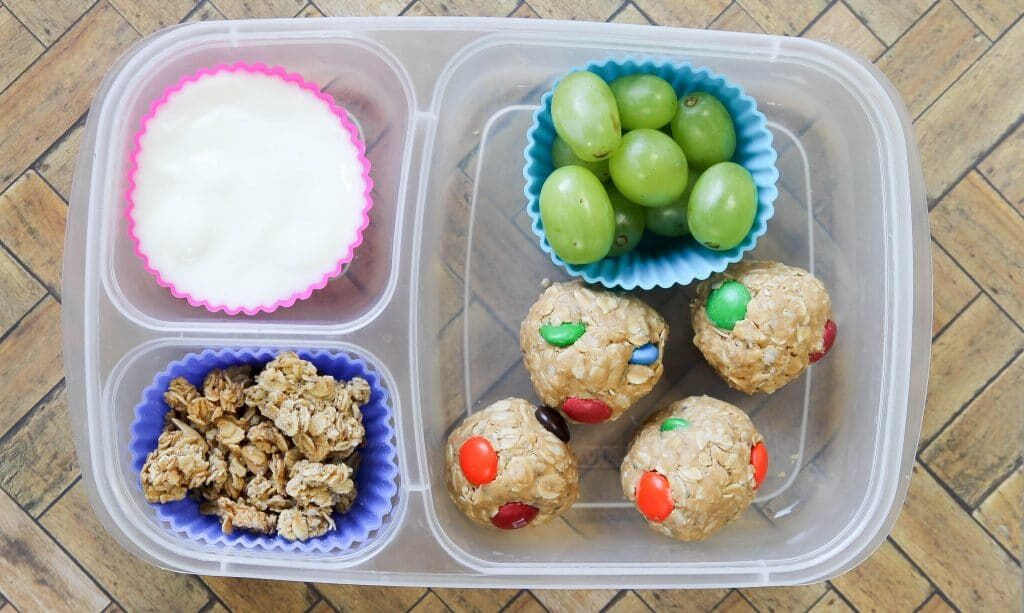 easy no bake cookie balls in a lunch container with grapes and yogurt