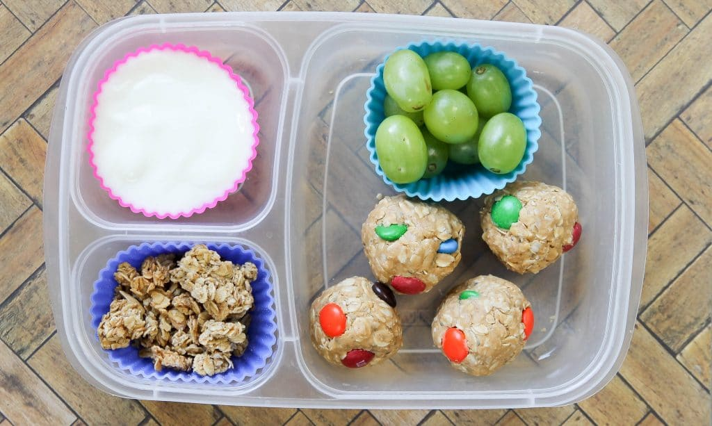 monster cookie dough balls in a lunch container with grapes and yogurt